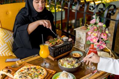 زوجان سعوديان خليجيان ، يقضيان اجواء رائعة سويا في المطعم ،العديد من أصناف الطعام و الماكولات على الطاولة ، متجر و مطعم سعودي