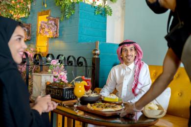 النادل يقدم الطعام لزوجين سعوديين خليجيين ، يقضيان اجواء رائعة سويا في المطعم ،العديد من أصناف الطعام و الماكولات على الطاولة ، متجر و مطعم سعودي