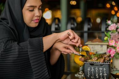 صورة مقربة لمائدة طعام خاصة بامراه سعودية خليجية ، تقضي اجواء رائعة  في المطعم ، العديد من أصناف الطعام و الماكولات على الطاولة ، متجر و مطعم سعودي