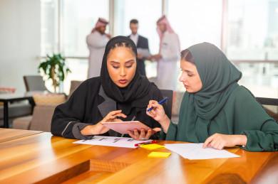 سيدتان اعمال سعوديات خليجيات في غرفة الاجتماعات داخل مقر الشركة ، و بالخلفية مجموعة رياديون من رجال الأعمال السعوديون , شركة سعودية ، شركاء عمل ، بيئة عمل ، وظيفة مكتبية ، عمل خليجي ،  فريق العمل