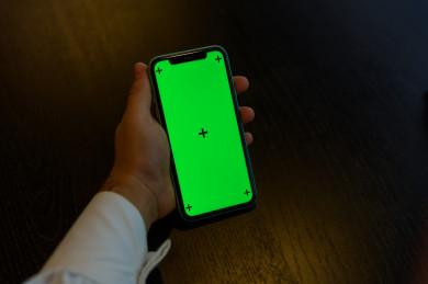 رجل أعمال سعودي خليجي يستخدام هاتفه المحمول بخلفية خضراء كروما ، تقنية و حاسب ، استخدام تقنية السمارت على الهاتف المحمول ليتحكم بالتلفاز