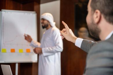 رجال اعمال خليجيون ، رجل سعودي في اجتماع عمل مع رجل اعمال اماراتي يتحدثون و يتناقشون حول استراتيجيات الشركة  ، لوحة بيضاء ،  تقديم الأفكار للزملاء في المكتب  ، اندماج شركة اماراتية و شركة سعودية ، بيئة عمل ، بيئة العمل
