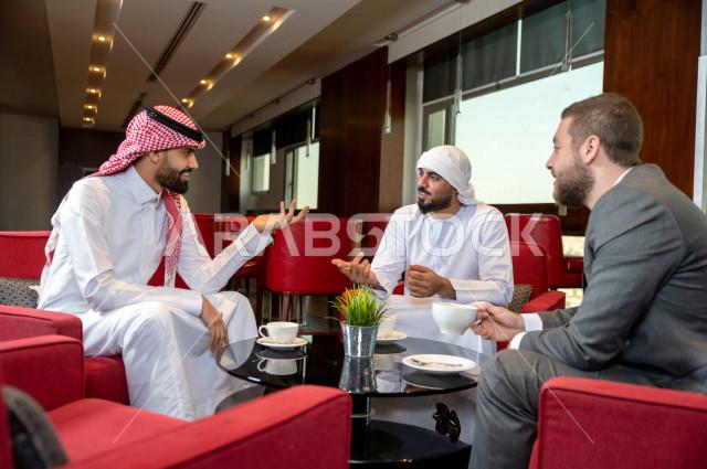 اجتماع عمل يضم رجال اعمال خليجيون مع السكرتير الخاص بالشركة ، رجل سعودي في اجتماع عمل مع رجل اعمال اماراتي ، شراكة عمل جديدة ، دارة الاعمال داخل مقر الشركة ، شركة اماراتيه ، بيئة العمل