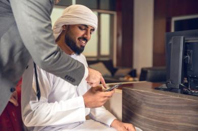 رجل اعمال اماراتي خليجي في مقر الشركة مع السكرتير الخاص فيه يدير المهام اليومية ،ادارة الاعمال داخل مقر الشركة ، شركة اماراتيه ، بيئة العمل