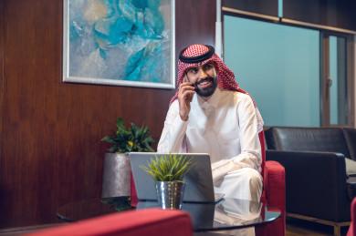 رجل اعمال سعودي خليجي على مكتبه و يعمل على الكمبيوتر المحمول ، اللباس السعودي التقليدي  ، شركة سعودية ، بيئة عمل