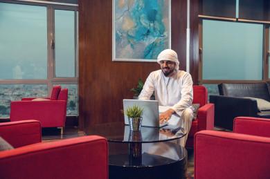 رجل اعمال اماراتي خليجي على مكتبه و يعمل على الكمبيوتر المحمول ، اللباس الاماراتي التقليدي  ، شركة اماراتيه، عمل الخليج ، وظيفة مكتبية ، بيئة عمل