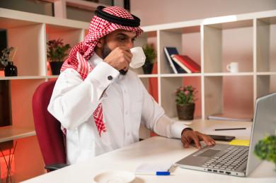 صورة مقربة لرجل اعمال سعودي خليجي يعمل في مقر الشركة ، يحتسي كوب من القهوه ، استراحة العمل  ،  يرتدي  لباس السعودي التقليدي  ، شركة سعودية ، عمل الخليج ، وظيفة مكتبية ، بيئة عمل