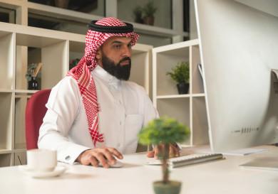 صورة مقربة لرجل اعمال سعودي خليجي يعمل في مقر الشركة ، يستخدم  جهاز تقني لانجاز مهامه  ،  يرتدي  لباس السعودي التقليدي  ، شركة سعودية ، عمل الخليج ، وظيفة مكتبية ، بيئة عمل