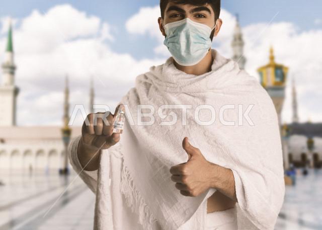 رجل مسلم عربي سعودي خليجي بلباس الاحرام ،  اتباع تعليمات و شروط الحج لعام 2021 ، اخذ جرعة اللقاح الآمنة ، التطعيم الأمن لكوفيد 19  ، فريضة الحج ، اداء مناسك الحج و العمرة ، مع خلفية للحرم المكي