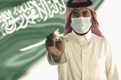 رجل عربي سعودي خليجي يحمل بيده اللقاح و يرتدي الكمامة الطبية ، اخذ جرعة اللقاح الآمنة ، التطعيم الآمن لكوفيد 19 ، التلقيح الطبي ، جرعة لتفادي الاصابة بالعدوى ، خلفية بعلم المملكة العربية السعودية