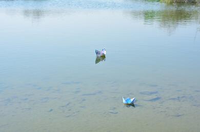 صورة مقربة لتيار المياه النقي في وادي الأخضر في مدينة جدة بالمملكة العربية السعودية ، انعكاس الطبيعة على المياه ، صورة مقربة لقارب من الورق صغير على مجرى المياه النقية في الوادي الأخضر بجدة ، أماكن سياحية