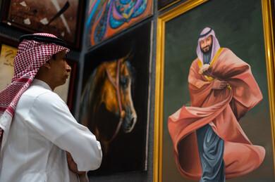 صورة لفنان عربي خليجي سعودي موهوب ينظر و يتأمل بلوحة فنية خاصة بسمو ولي العهد الأمير محمد بن سلمان ، ذكرى اليوم الوطني السعودي ، الاحتفال بالعيد الوطني السعودي