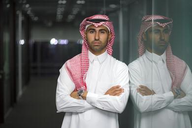 صورة مقربة لرجل أعمال عربي سعودي خليجي مع خلفية المكتب  ، يرتدي الزي السعودي التقليدي ، بأيدي متقاطعه في مقرعمله بالشركة ، شركة سعودية ، وظائف ومهن مكتبية ، بيئة العمل