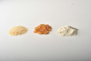 مجموعة من الأرز والزبيب والطحين مصورة على خلفية بيضاء .